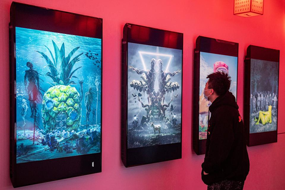 A man looks at digital paintings by US artist Beeple at a crypto art exhibition entitled Virtual Niche: Have You Ever Seen Memes in the Mirror?, one of the world's first physical museum shows of blockchain art, ahead of its opening in Beijing on March 26, 2021. - RESTRICTED TO EDITORIAL USE - MANDATORY MENTION OF THE ARTIST UPON PUBLICATION - TO ILLUSTRATE THE EVENT AS SPECIFIED IN THE CAPTION (Photo by NICOLAS ASFOURI / AFP) / RESTRICTED TO EDITORIAL USE - MANDATORY MENTION OF THE ARTIST UPON PUBLICATION - TO ILLUSTRATE THE EVENT AS SPECIFIED IN THE CAPTION / RESTRICTED TO EDITORIAL USE - MANDATORY MENTION OF THE ARTIST UPON PUBLICATION - TO ILLUSTRATE THE EVENT AS SPECIFIED IN THE CAPTION (Photo by NICOLAS ASFOURI/AFP via Getty Images)