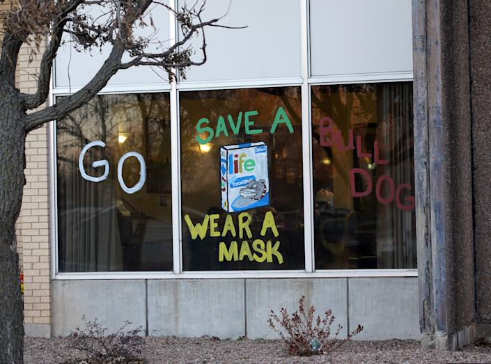 A sign on the Gove County Medical Center's nursing home reminds the public to wear a mask. Workers there painted the sign after a COVID-19 infection rampaged through the facility, killing 17 people.