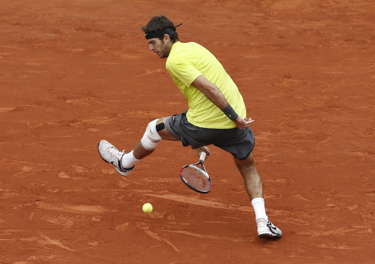 Juan Martin del Potro of Argentina scores a point as he hits the ball with his racket between his legs in his quarter final match against Roger Federer of Switzerland at the French Open tennis tournament in Roland Garros stadium in Paris, Tuesday June 5, 2012. (AP Photo/Bernat Armangue)