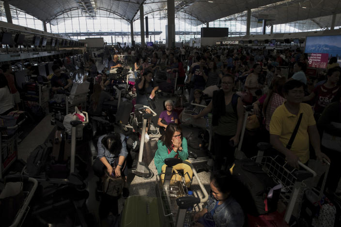 A beam of sunlight is cast on the travelers as they wait at the check-in counters in the departure hall of the Hong Kong International Airport in Hong Kong, Tuesday, Aug. 13, 2019. (Photo: Vincent Thian/AP)