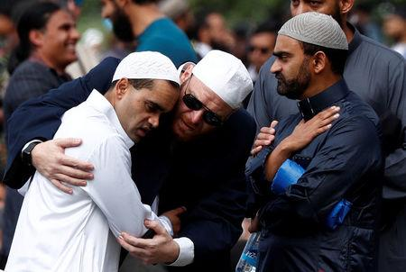 FILE PHOTO: People comfort each other before the Friday prayers at Hagley Park outside Al-Noor mosque in Christchurch