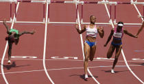 Jasmine Camacho-Quinn, of Puerto Rico, center, celebrates after winning the gold in the women's 100-meters hurdles final ahead of Kendra Harrison, of United States, silver, right, and Tobi Amusan, of Nigeria, fourth, at the 2020 Summer Olympics, Monday, Aug. 2, 2021, in Tokyo, Japan. (AP Photo/Charlie Riedel)