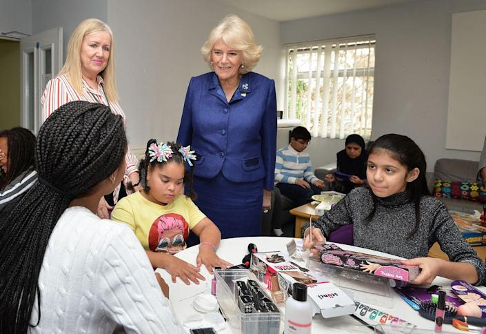 <p>The Duchess of Cornwall wore a royal blue suit that she accessorized with two broaches and pearl drop earrings for a visit to one of her royal patronages, the Barnardo's charity. </p>