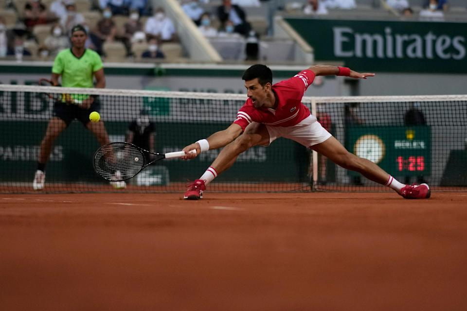 Novak Djokovic stretches for a backhand with Rafael Nadal watching (AP)