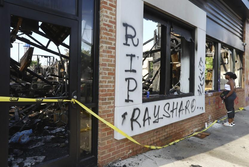 FILE - In this June 15, 2020 file photo, a woman looks at the interior of the burned Wendy's restaurant in Atlanta. Investigators said Saturday, June 20, they have issued an arrest warrant for a woman in the burning of a Wendy's restaurant in Atlanta during protests over the police shooting of Rayshard Brooks. (Curtis Compton/Atlanta Journal-Constitution via AP)
