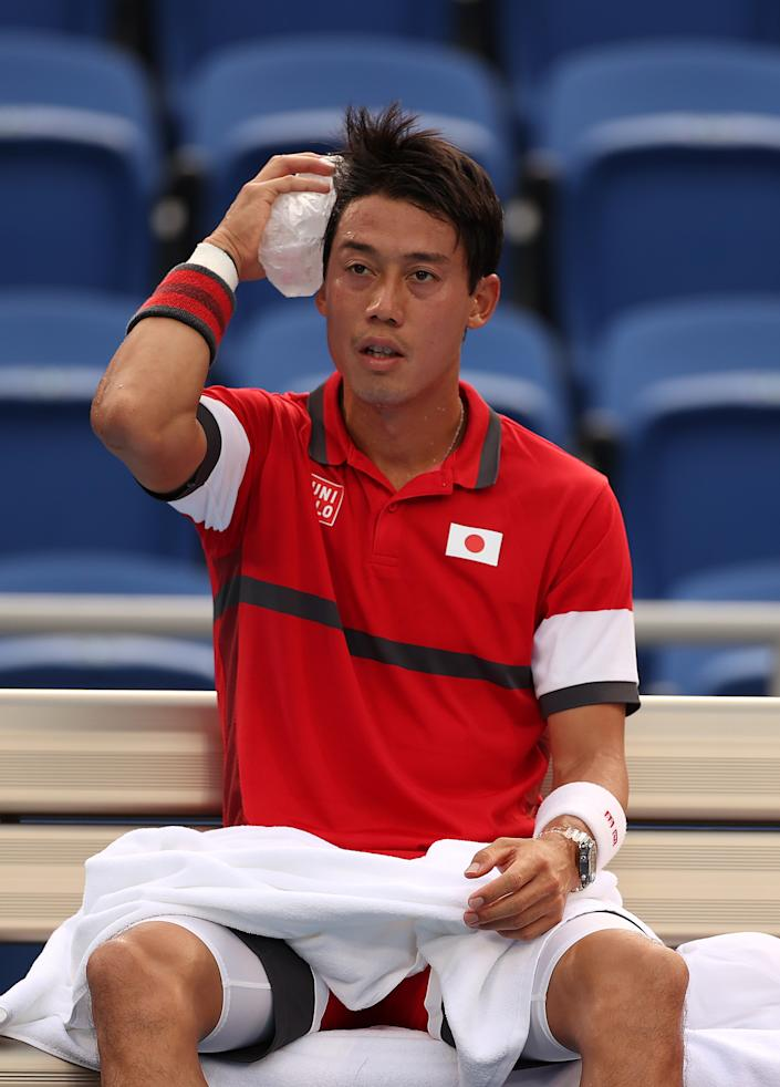 <p>Kei Nishikori of Team Japan applies an ice pack to his head during his Men's Singles Second Round match against Marcos Giron of Team USA on day four of the Tokyo 2020 Olympic Games at Ariake Tennis Park on July 27, 2021 in Tokyo, Japan. (Photo by David Ramos/Getty Images)</p>