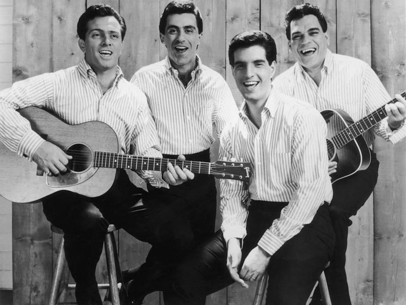 circa 1965: Promotional portrait of the American pop group The Four Seasons. From left: Tommy DeVito, Frankie Vali, Bob Gaudio, and Nick Massi. The band members are dressed identically in light striped shirts and black pants. (Photo by Hulton Archive/Getty Images)