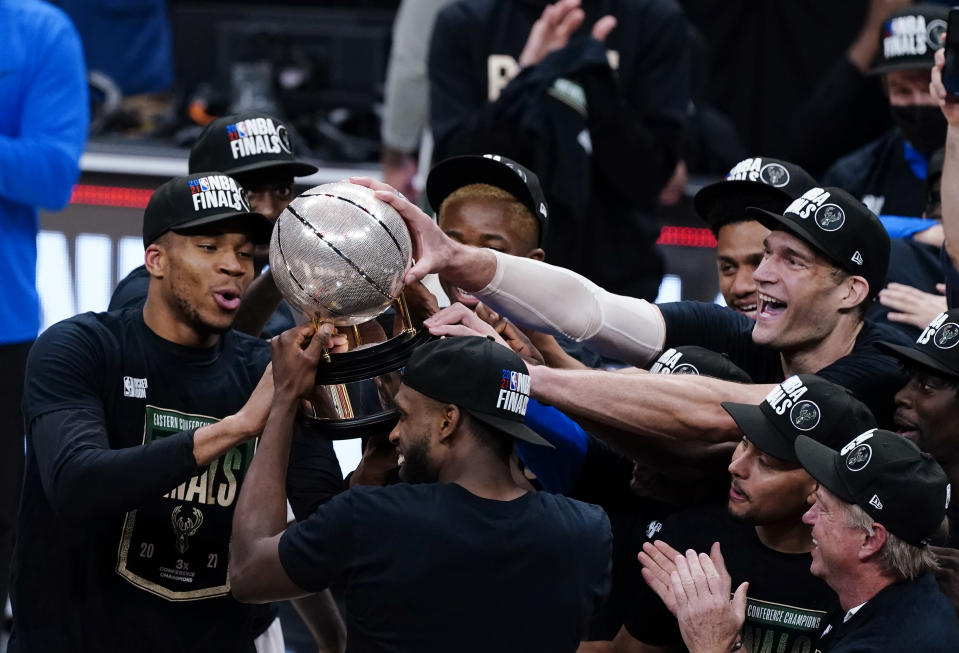 The Milwaukee Bucks hoist the trophy after defeating the Atlanta Hawks in Game 6 of the Eastern Conference finals of the NBA basketball playoffs, advancing to the NBA Finals, Saturday, July 3, 2021, in Atlanta. (AP Photo/John Bazemore)