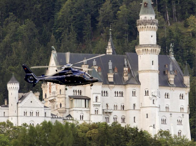 A helicopter of the German Federal  Police passes the famous Neuschwanstein Castle near Schwangau, Germany  Saturday Aug. 13, 2011. Authorities say 20 tourists who had been trapped overnight in a gondola in southern Germany's Alps could be safely freed.  Emergency service spokesman Roland Ampenberger says helicopter crews rescued the tourists, including several children, early Saturday morning after they had spent about 17 hours inside the gondola. Police say the gondola was blocked Friday after a paraglider crashed into the teleferic's cables, but strong winds hindered a swift rescue effort. Tegelberg mountain is within sight of one of Germany's popular tourist attractions, the Neuschwanstein Castle which is often viewed as the inspiration for one of Walt Disney's fairy tale castles. (AP Photo/dapd/Sebastian Widmann/dapd)