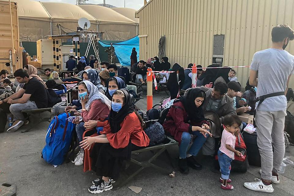 People wait to be evacuated from Afghanistan at the airport in Kabul on August 18, 2021 following the Taliban stunning takeover of the country. (Photo by - / AFP) (Photo by -/AFP via Getty Images)