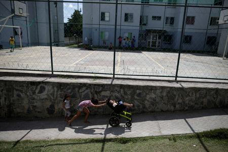 "Luana Vieira, who is two years old, and was born with microcephaly, is pushed in a wheelchair by her sister Vitoria Evillen, near a sports court in the housing complex where they live, in Olinda, Brazil, August 6, 2018. Luana's mother Rosana Vieira Alves has three daughters. ""It's hard to manage the girls. Some of them are jealous, but Luana needs more care. In time, they'll understand."" Rosana does not have any family support and is overwhelmed by the cost of housing and Luana's medicines. She counts it a victory that she has managed to get a wheelchair for Luana, and worries about the four surgeries her daughter needs to correct problems with her eyes, her gut and the position of her hips and feet. The demands have taken Rosana to some dark places, and she confesses that she has considered suicide. But she still dreams of a better future, and hopes to get a degree in accounting or civil engineering. REUTERS/Ueslei Marcelino"