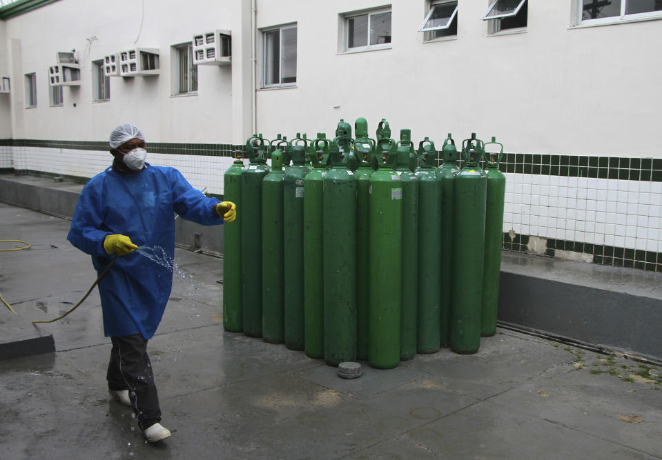 A health worker cleans the area where empty oxygen tanks stand idle at Joventina Dias Hospital in Manaus, Brazil, Friday, Jan. 15, 2021. Hospital staff and relatives of COVID-19 patients rushed to provide facilities with oxygen tanks just flown into the city as doctors chose which patients would breathe amid dwindling stocks and an effort to airlift some of them to other states. (AP Photo/Edmar Barros)