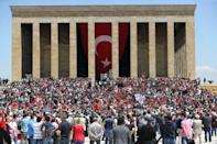 People hold Turkish flags in front of the mausoleum of Mustafa Kemal Ataturk in Ankara, on May 19, 2016
