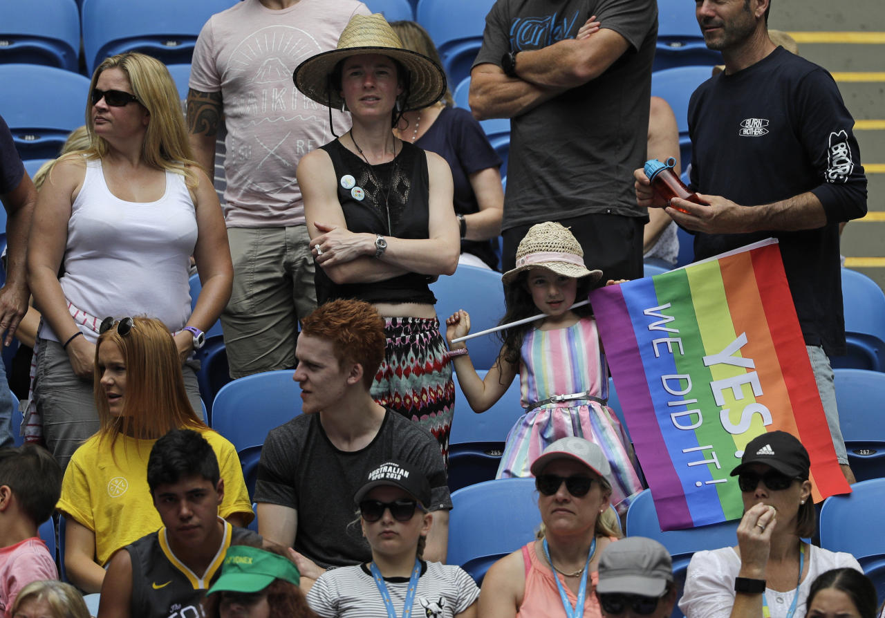 A fan waves a rainbow flag while watching the first round match on Margaret Court Arena between United States' Sloane Stephens and China's Zhang Shuai at the Australian Open tennis championships in Melbourne, Australia, Monday, Jan. 15, 2018. Marriage equality proponents draped themselves in rainbow flags at Margaret Court Arena on the first day of the Australian Open to protest Australian tennis great Margaret Court's controversial views on gay marriage and the broader lesbian, gay, bisexual and transgender community. (AP Photo/Dita Alangkara)