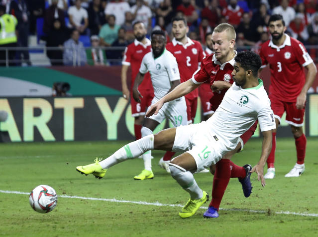 Saudi Arabia's midfielder Hussain Al-Mogahwi, foreground, kicks the ball as he scores his goal celebrates during the AFC Asian Cup group E soccer match between Lebanon and Saudi Arabia at Al Maktoum Stadium in Dubai, United Arab Emirates, Saturday, Jan. 12, 2019. (AP Photo/Hassan Ammar)