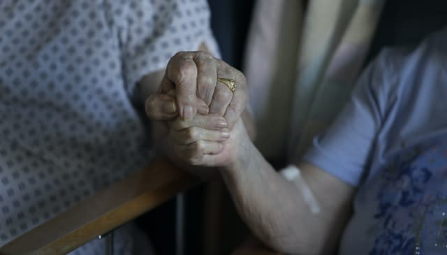 A husband and wife hold hands in a hospital