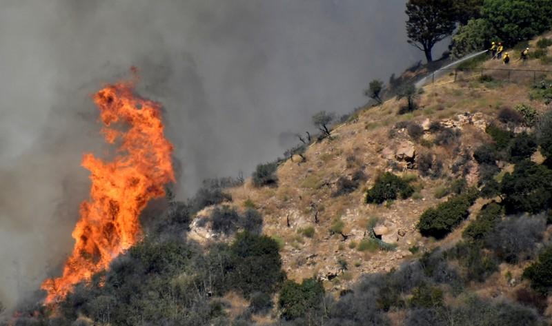 Firefighters battle a blaze that was threatening homes in the Pacific Palisades community of Los Angeles, California