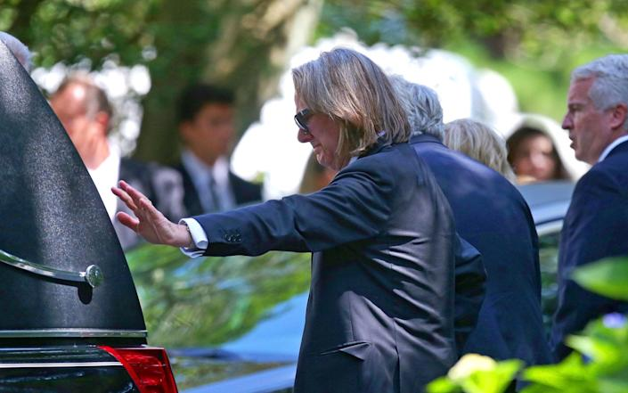 A distraught Paul Michael Hill, Saoirse's father, places his hand on the hearse - Pool The Boston Globe