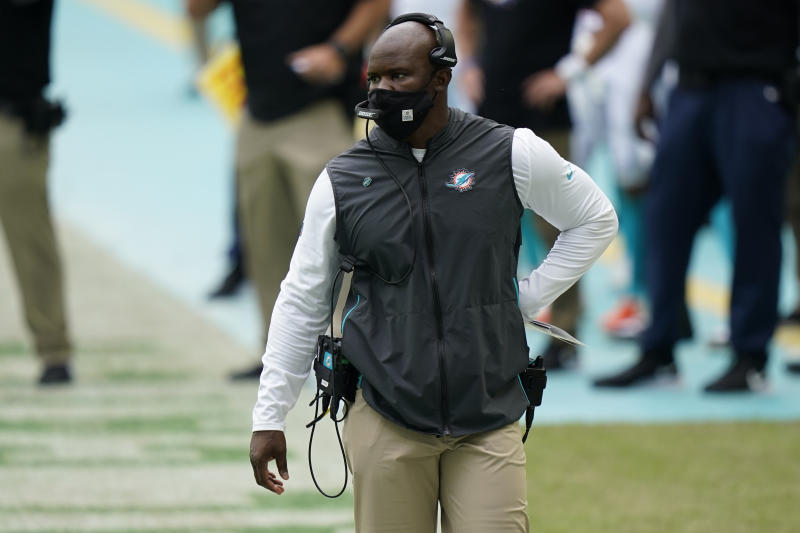 Brian Flores, wearing a mask and a headset, walks the sideline during a game.