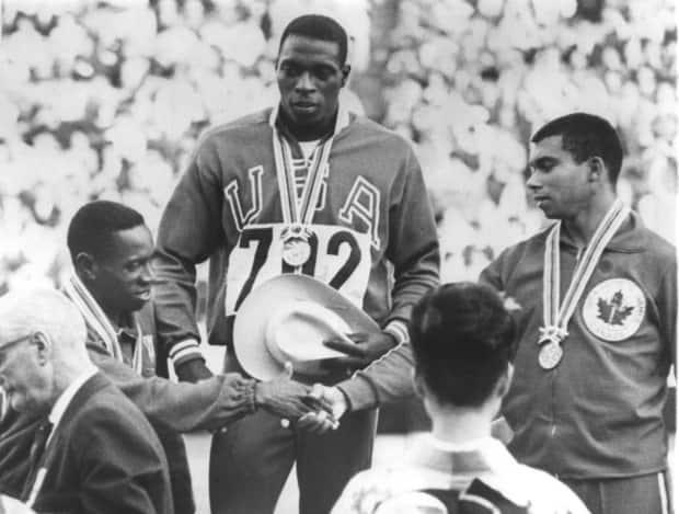 Oct 15, 1964:  Olympic gold medal winner Robert Hayes watches as silver medal winner Enrique Figuerola congratulates bronze medallist Harry Jerome, right.