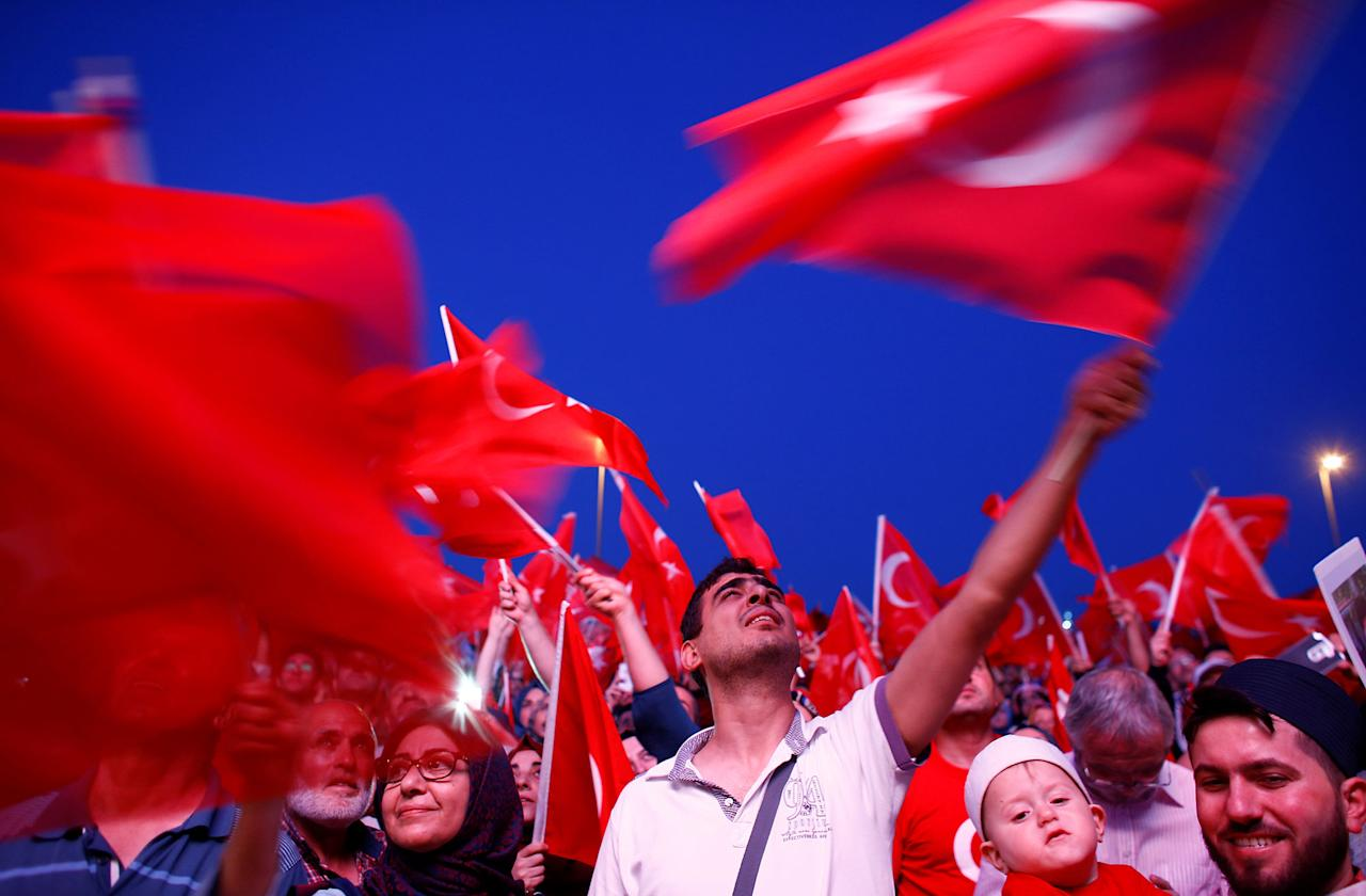 <p>People wave Turkey's national flags as they attend a ceremony marking the first anniversary of the attempted coup at the Bosphorus Bridge in Istanbul, Turkey, July 15, 2017. (Photo: Osman Orsal/Reuters) </p>