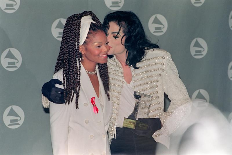 "US pop star and entertainer Micheal Jackson kisses his sister Janet Jackson (L) after she presented him with the Grammy Legend Award at the 35th Annual Grammy Awards February 24,1993. Michael Jackson died on June 25, 2009 after suffering a cardiac arrest, sending shockwaves sweeping across the world and tributes pouring in on June 26 for the tortured music icon revered as the ""King of Pop."" AFP PHOTO/Scott FLYNN (Photo by SCOTT FLYNN / AFP) (Photo credit should read SCOTT FLYNN/AFP/Getty Images)"