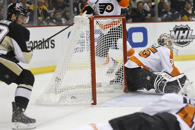 Pittsburgh Penguins' Jayson Megna, left, scores on Philadelphia Flyers goalie Steve Mason (35) during the second period of an NHL hockey game on Sunday, March 16, 2014, in Pittsburgh. (AP Photo/Keith Srakocic)
