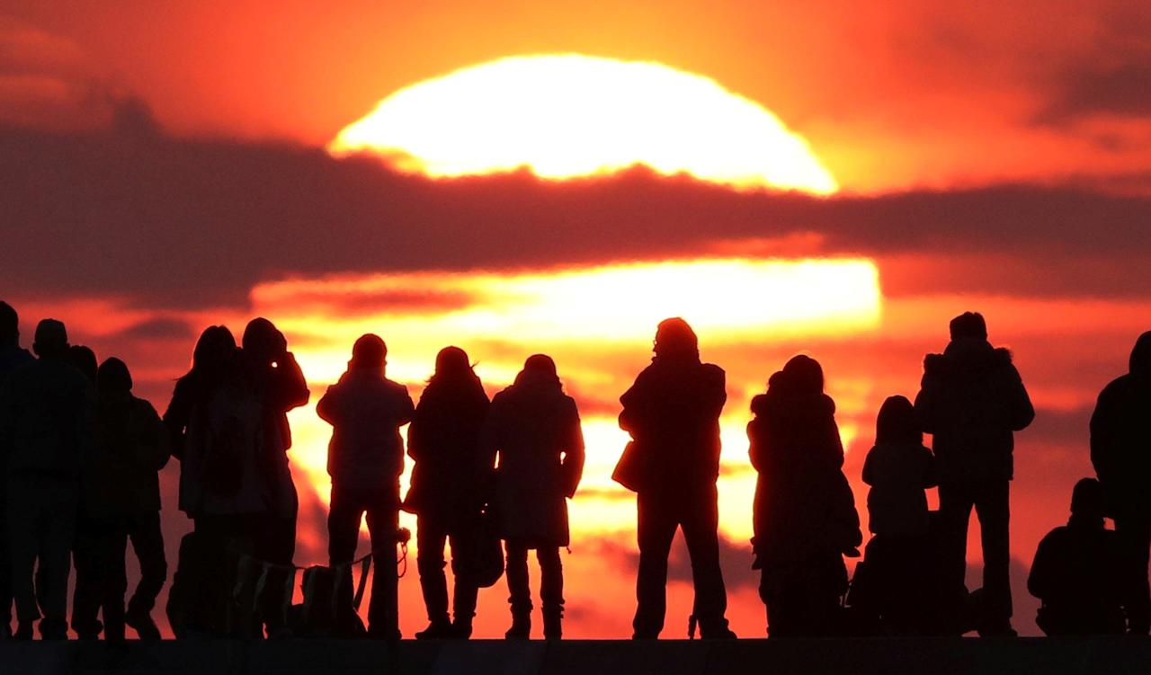 People watch the first sunrise on New Year's Day at Yuriage district where an area was damaged by the March 11, 2011 earthquake and tsunami, in Natori, Miyagi prefecture, Japan, in this photo taken by Kyodo January 1, 2017. Mandatory credit Kyodo/via REUTERSATTENTION EDITORS - THIS IMAGE WAS PROVIDED BY A THIRD PARTY. EDITORIAL USE ONLY. MANDATORY CREDIT. JAPAN OUT. NO COMMERCIAL OR EDITORIAL SALES IN JAPAN.