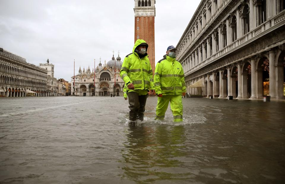 "Men wearing waterproof gear walk across a flooded St. Mark's Square on December 8, 2020 following a high tide ""Alta Acqua"" event following heavy rains and strong winds, and the mobile gates of the MOSE Experimental Electromechanical Module that protects the city of Venice from floods, were not lifted. (Photo by ANDREA PATTARO / AFP) (Photo by ANDREA PATTARO/AFP via Getty Images)"