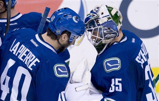 Vancouver Canucks' Maxim Lapierre (40) celebrates his teams win with Vancouver Canucks goalie Cory Schneider (35) following a shootout where Lapierre got the game winning goal during NHL hockey action against the Columbus Blue Jackets in Vancouver, British Columbia, Tuesday, March 26, 2013. (AP Photo/The Canadian Press, Jonathan Hayward)