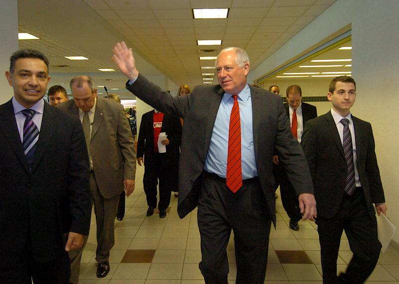 Illinois Governor Pat Quinn and Motorola Mobility Chairman and CEO Dr. Sanjay Jha, left, announced Friday, May 6, 2011,that the Motorola Mobility Inc. corporate headquarters will be located in Libertyville, Illinois. Here Quinn waves to employees at the Motorola facility. (AP Photo/Daily Herald, Bob Chwedyk) ** MANDATORY CREDIT **