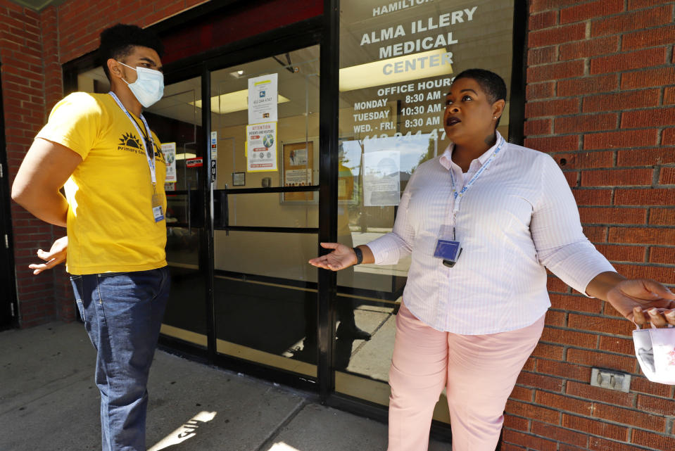 In this photo made on Monday, July 20, 2020, Kiva A. Fisher-Green, right, talks with fellow social worker Tyree R. Ford outside the Alma Illery Medical Center in Pittsburgh. In March and April when Philadelphia and its surroundings became one of the nation's hot-spots for COVID-19 cases, Pittsburgh seemed at the time, to be under more control: the city racked up a fraction of the coronavirus cases as the other side of Pennsylvania. But by the beginning of July, officials in Pittsburgh's Allegheny County, began a cascading shutdown of bars, restaurants and gatherings due to an alarming spike in COVID-19 cases. (AP Photo/Gene J. Puskar)