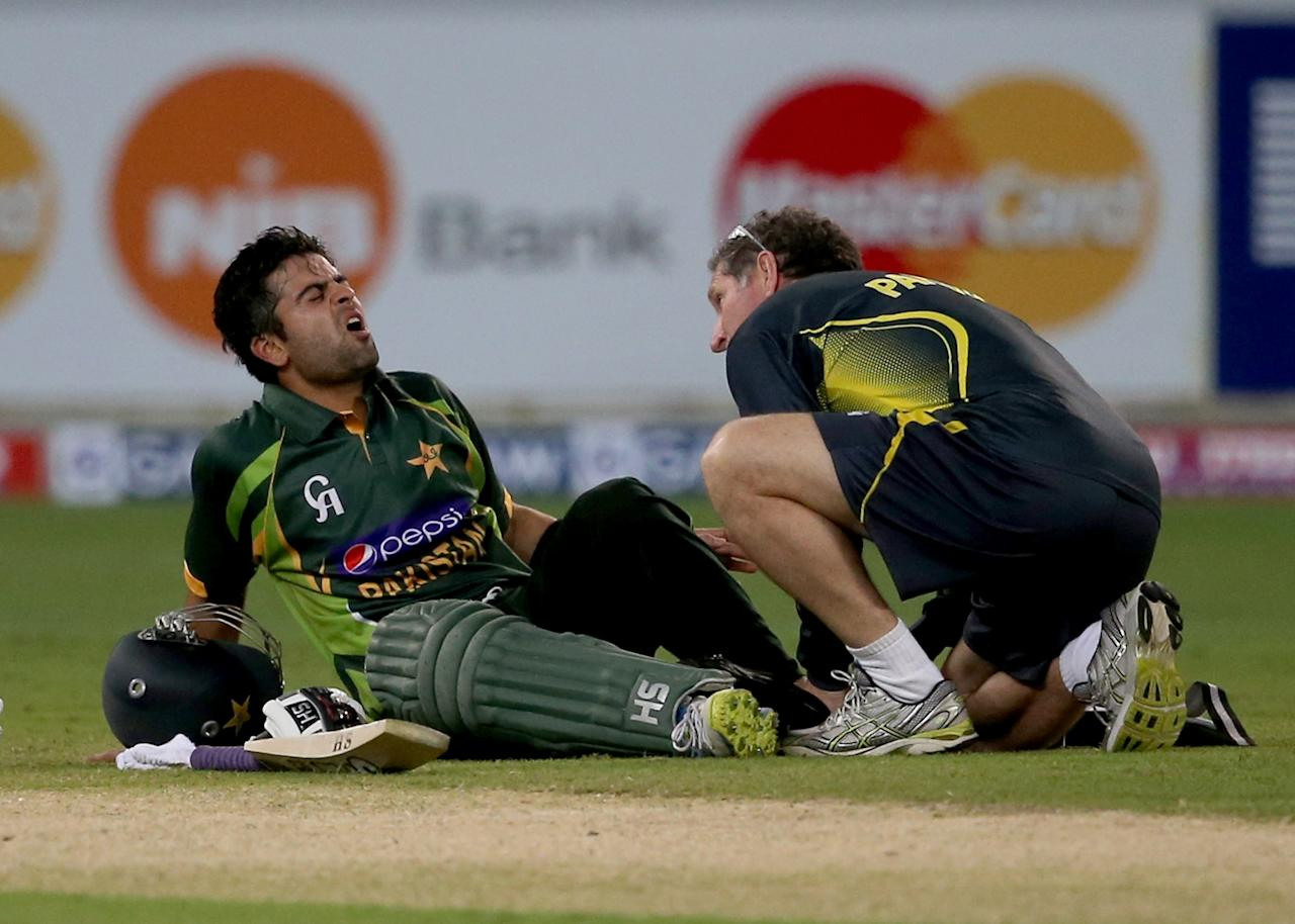 DUBAI, UNITED ARAB EMIRATES - DECEMBER 20:  Ahmed Shahzad of Pakistan receives treatment to his foot after being struck by a delivery of Lasith Malinga during the second One-Day International (ODI ) match between Sri Lanka and Pakistan at the Dubai Sports City Cricket Stadium on December 20, 2013 in Dubai, United Arab Emirates.  (Photo by Francois Nel/Getty Images)