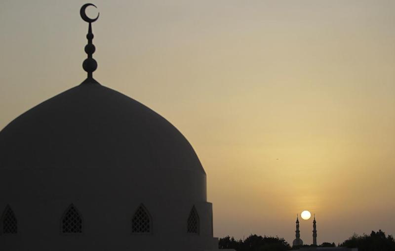 FILE - This Saturday, July 20, 2013 file photo shows sun setting behind minarets of a mosque a few minutes before Iftar, the meal served at dusk when Muslims break their day-long fast during the month of Ramadan, in Dubai, United Arab Emirates. Dubai's Islamic-influenced laws on sex, morality and how they are applied are now center stage in a global debate following the legal battle of a 24-year-old Norwegian woman, Marte Deborah Dalelv. She was sentenced to 16 months in prison on unwed sex and alcohol charges last week after claiming she was raped by a co-worker in March.(AP Photo/Kamran Jebreili, File)