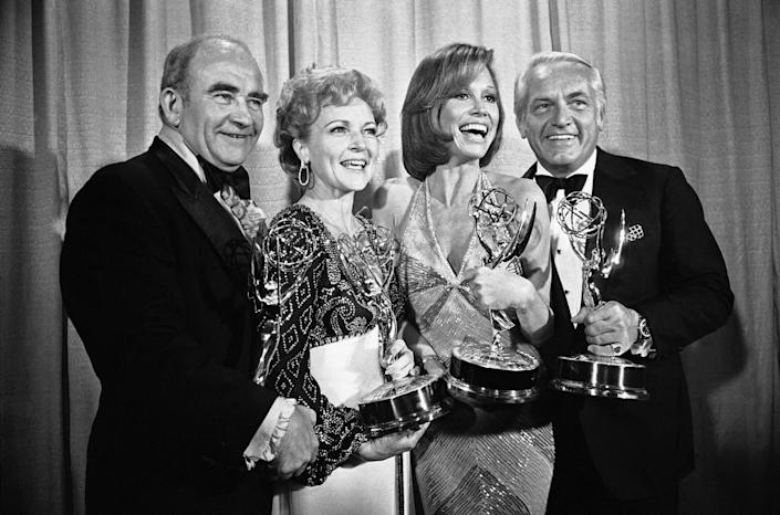 Two men and two women hold Emmy statuettes