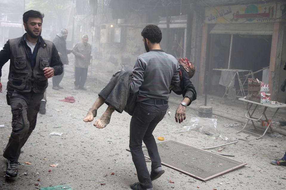 resident carries an injured man through a site damaged from what activists said was an airstrike by forces loyal to Syria's President Bashar al-Assad on the main field hospital in the town of Douma, eastern Ghouta in Damascus October 29, 2015.