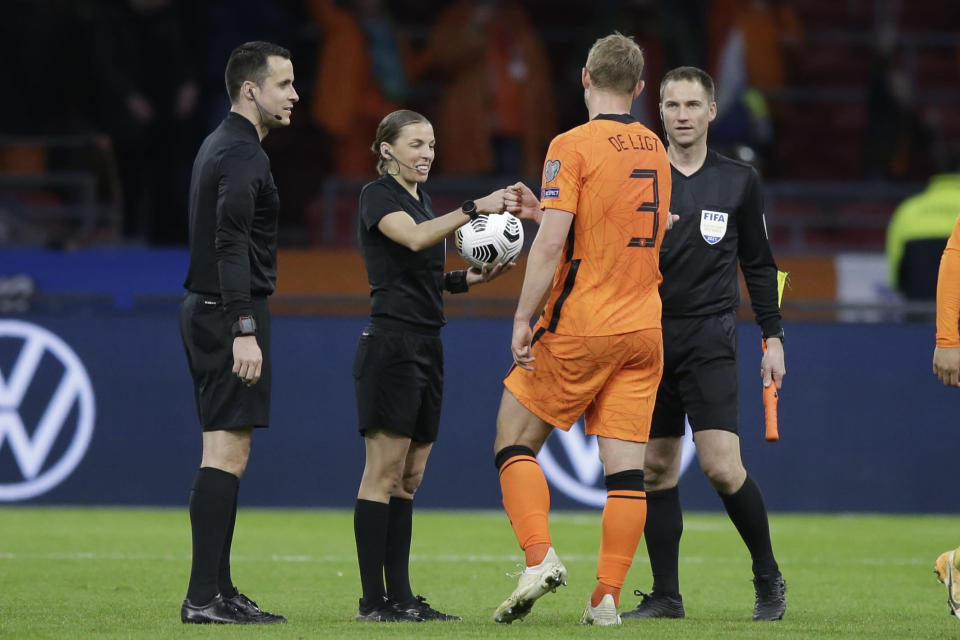Referee Stephanie Frappart cheers with Netherlands' Matthijs de Ligt at the end of the World Cup 2022 group G qualifying soccer match between The Netherlands and Latvia at the Johan Cruyff ArenA in Amsterdam, Netherlands, Saturday, March 27, 2021. (AP Photo/Peter Dejong)
