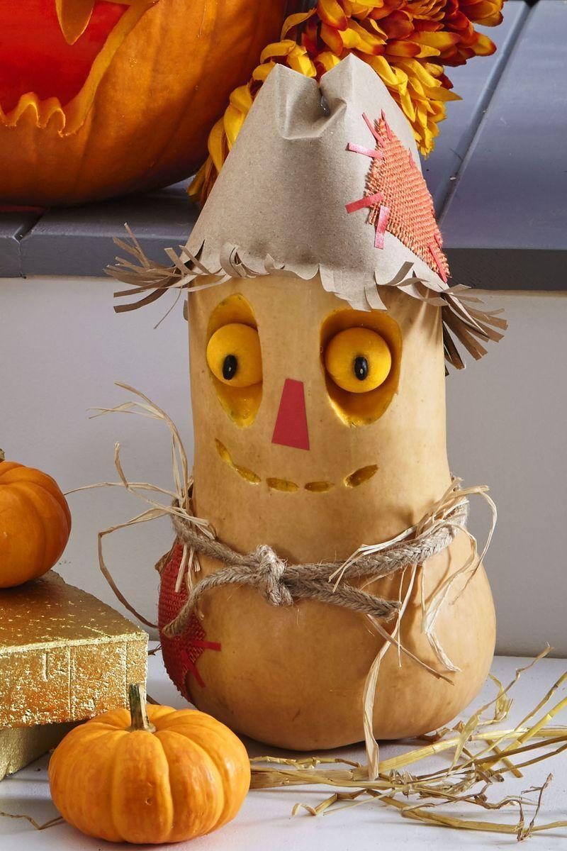 <p>We promise this sweet fella, made out of a butternut squash, won't scare away any Halloween party guests.</p><p><strong>Make the Scarecrow Pumpkin:</strong> Use a melon baller to scoop out two eyes from a butternut squash; reserve. Etch out eye sockets and mouth with a linoleum cutter. Use toothpicks to secure eyes in sockets. Push in dried black bean pupils; secure with toothpicks. <br></p><p>Cut a piece of red masking tape and attach for nose. For hat, make a cone from a paper bag, then fold in its top and fringe its bottom, curling upward. Cut patches from burlap and attach with small masking tape strips. Tie cord ribbon around middle for a belt and tuck in straw. <br></p>