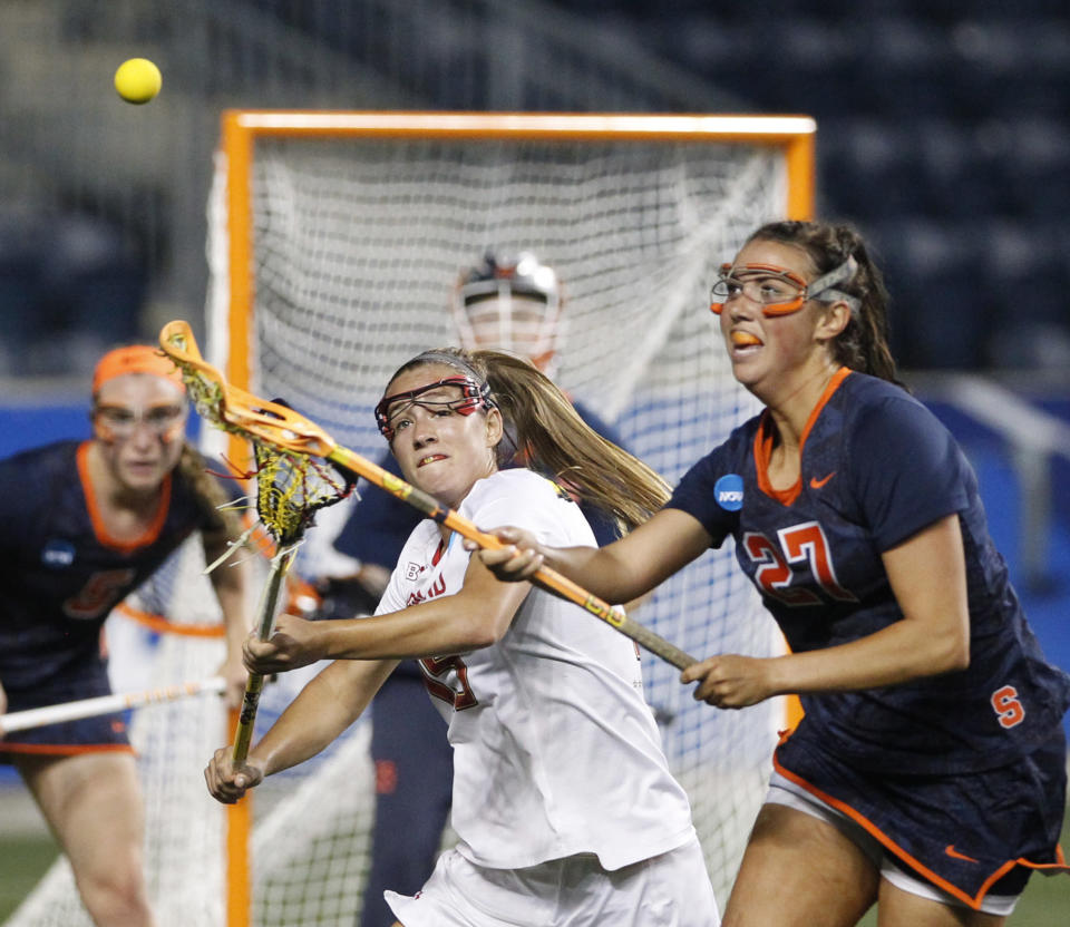 FILE - Maryland's Jen Giles, center, and Kelly Cross, right, of Syracuse, compete for the ball during the first half of a semifinal in the NCAA Division I women's lacrosse tournament in Chester, Pa., in this Friday, May 27, 2016, file photo. Brad Hurlbut took over as the athletic director at Fairleigh Dickinson in 2019, planning to increase the number of sports played at the small Division I school a short ride from New York City. In a little over two years, Hurlbut has taken his first step, announcing last month that men's volleyball will be added in 2021-22 and women's lacrosse would follow the next year.(Charles Fox/The Philadelphia Inquirer via AP, File)
