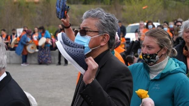 Héctor Vila, bishop of the Roman Catholic Diocese of Whitehorse, held a pair of children's shoes as he stood among the demonstrators in Whitehorse on Monday afternoon.