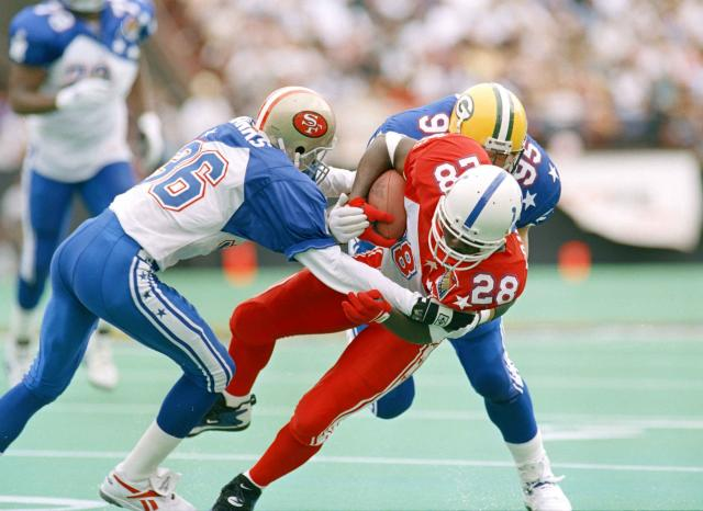 File- This Feb. 5, 1995, file photo shows Baltimore Colts running back Marshall Faulk (28) being pulled down by San Francisco 49ers safety Merton Hanks (36) and Green Bay Packers Bryce Paup during the second quarter of the Pro Bowl in Honolulu. TV ratings for the Pro Bowl lag below all the prime time regular season games, and the on-field intensity and drama that fuels so much of the national interest in the sport is nonexistent. The annual all-star exhibition does not lack for history, however, with a genesis traced back to the 1938 season. (AP Photo/Eric Gay, File)
