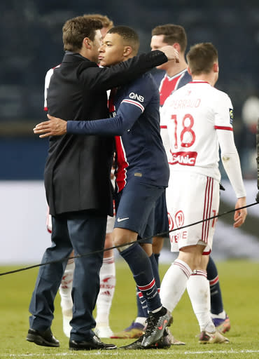 PSG's head coach Mauricio Pochettino greets PSG's Kylian Mbappe after the French League One soccer match between Paris Saint-Germain and Brest at the Parc des Princes in Paris, Saturday, Jan. 9, 2021. PSG won the match 3-0. (AP Photo/Francois Mori)
