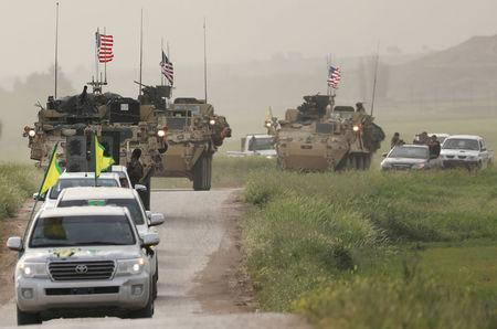 FILE PHOTO: Kurdish fighters from the People's Protection Units (YPG) head a convoy of U.S military vehicles in the town of Darbasiya next to the Turkish border