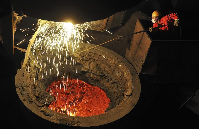 An employee works above a furnace containing molten steel at a factory of Dongbei Special Steel Group Co. Ltd. in Dalian