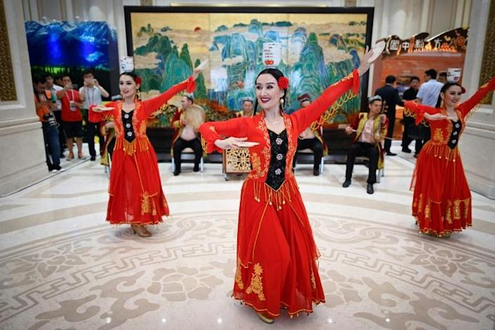 Ethnic-minority artists performed a traditional dance before officials held a press conference for the Xinjiang Uyghur Autonomous Region in Beijing (AFP Photo/WANG ZHAO)