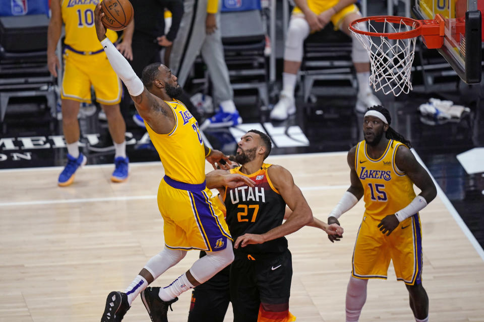 Los Angeles Lakers forward LeBron James, left, goes to the basket as Utah Jazz center Rudy Gobert (27) defends during the first half of an NBA basketball game Wednesday, Feb. 24, 2021, in Salt Lake City. (AP Photo/Rick Bowmer)