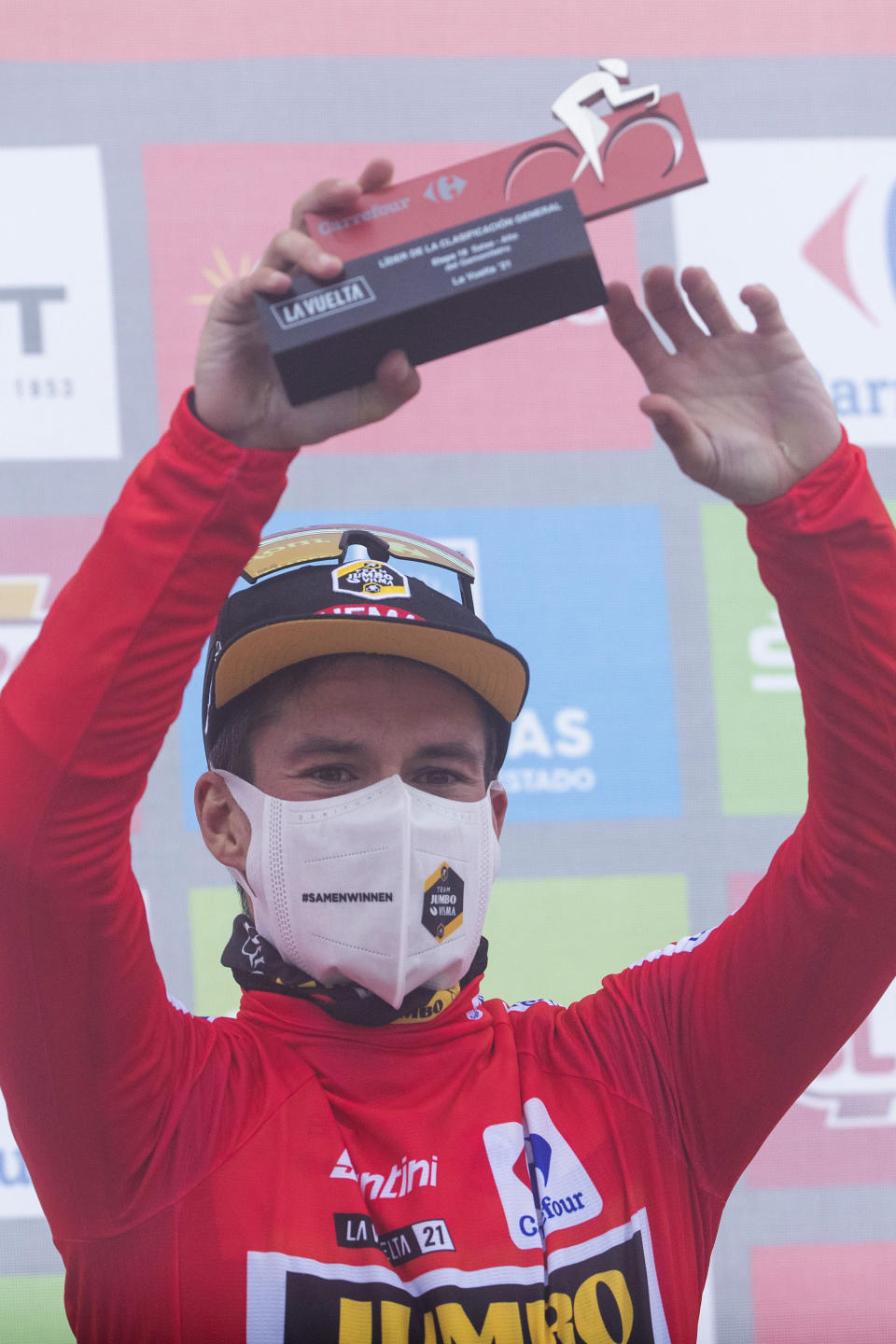 Primoz Roglic of Slovenia wears the red-shirt La Vuelta leader on the podium at the end the 18th stage between Salas and Alto del Gamoniteiro, during La Vuelta cycling race in Spain, Thursday Sept. 2, 2021. (AP Photo/Lalo R. Villar)
