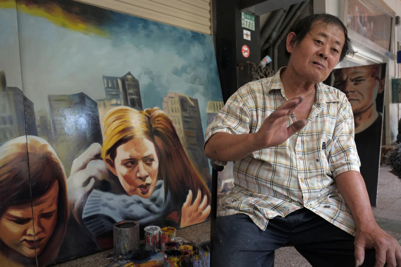 In this Friday, Sept. 6, 2013 photo, local artist Yan Jhen-fa describes his career of painting movie posters at his makeshift sidewalk studio for the Chuan Mei Theater in Tainan, Taiwan. The Chuan Mei's main attraction is the colorful 3-meter (9-foot) -square oil-painted advertising posters hung above the theater entrance to illustrate the daily bill of fare. They are the life work of 61-year-old Yan, the last practitioner of this once-popular art form in the country. (AP Photo/Wally Santana)