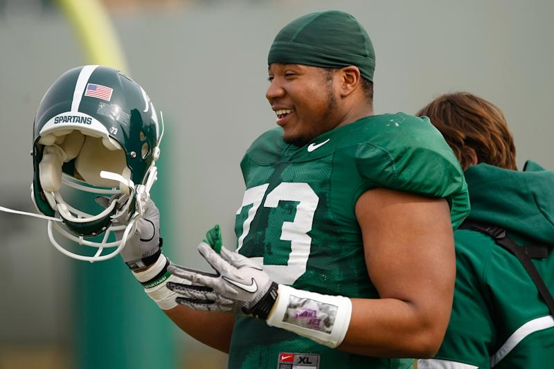 In a photo taken April 7, 2011 and provided by the Michigan State University Athletic Communications, offensive lineman Arthur Ray Jr., participates in the team's spring NCAA college football practice on April 7, 2011, in East Lansing, Mich. Around the same time he signed with MSU back in 2007, Ray found out he had cancer in his leg. Four years and several operations later, he's back on the field. (AP Photo/Michigan State University, Matthew Mitchell)