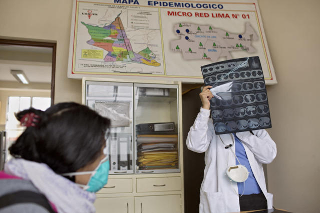 <p>Shortly after getting on HIV medication, Tamara is diagnosed with tuberculosis. Here, a doctor examines an x-ray of her lungs. (Photo: Danielle Villasana) </p>